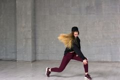 Young pretty skillful rap dancer. A beautiful young hip hop dancer dancing contemporary urban street dance in studio Royalty Free Stock Image