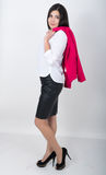 A young pretty slim asian woman standing in a leather skirt and white blouse. holding a red jacket on shoulderl.  Stock Photos