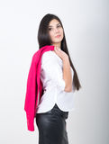 A young pretty slim asian woman standing in a leather skirt and white blouse. holding a red jacket on shoulderl.  Royalty Free Stock Image
