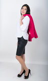A young pretty slim asian woman standing in a leather skirt and white blouse. holding a red jacket on shoulderl.  Royalty Free Stock Photos