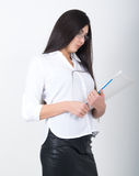 A young pretty slim asian woman in a white blouse, black leather skirt and glasses holding a folder with documents Stock Photography