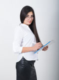 A young pretty slim asian woman in a white blouse, black leather skirt and glasses holding a folder with documents Stock Photo