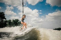 The ladys wakeboard is towed behind a motorboat by rope. The young pretty slim brunette ladys wakeboard is towed behind a motorboat by steel wire rope stock images