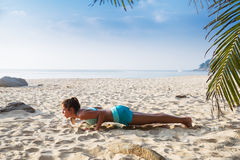 Young pretty slim brunette woman practise yoga pose on tropical Stock Photography