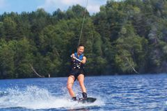 Young pretty slim brunette woman riding wakeboard on wave of mot. Orboat in a summer lake Stock Images
