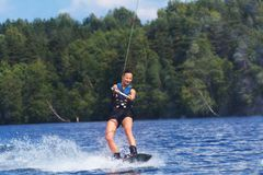 Young pretty slim brunette woman riding wakeboard on wave of mot. Orboat in a summer lake Stock Photography