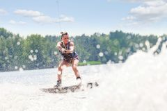 Young pretty slim brunette woman riding wakeboard on wave of mot. Orboat in a summer lake Stock Photos