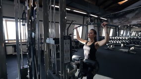 Young pretty slim woman do exercises on training machine in gym. Adult caucasian redheaded lady with tattoo, hair in ponytail in black sportswear with gold stock footage