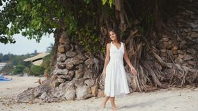 Young pretty smiles woman with long hair in white drees walks on a tropical beach Stock Image