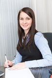Young pretty smiling business woman. With notebook in the office Stock Images