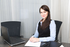 Young pretty smiling business woman. With notebook in the office Royalty Free Stock Image