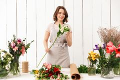 Pretty smiling florist woman with different flowers. Young pretty smiling florist woman standing near table with different flowers and looking aside in workshop Royalty Free Stock Images