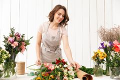 Pretty smiling florist woman with different flowers. Young pretty smiling florist woman standing near table with different flowers and looking aside in workshop Stock Photos