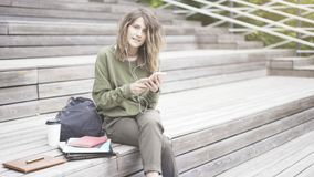 A young smiling girl is holding a phone outdoors sitting on the stairs. A young pretty smiling girl dressed in a green sweat shirt is listening to music outdoors royalty free stock photography