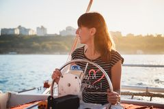 Young pretty smiling girl in striped shirt and white shorts driving luxury yacht in sea, hot summer day, sunset stock photos