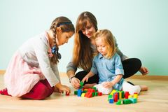 Young nanny playing with kids while babysitting. Young pretty smiling nanny playing with two girls sitting on a floor. Woman building towers with two adorable royalty free stock image