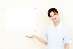 Young pretty smiling nurse welcoming you royalty free stock images