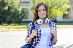 Young pretty smiling student with backpack and headphones standing against university royalty free stock photo