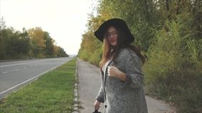 Young pretty smiling woman in black hat and glasses posing on the autumn street. And look at the camera stock video