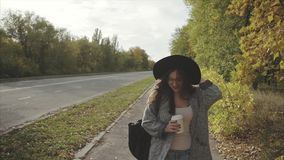 Young pretty smiling woman in black hat walking down the autumn street stock video