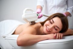 Young pretty smiling woman back laser epilation in beauty salon. Cosmetologist doing depilation treatment with elos royalty free stock photography