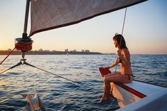 Young pretty smiling woman at luxury yacht in sea, looking forward, sunset evening time.  Royalty Free Stock Photos