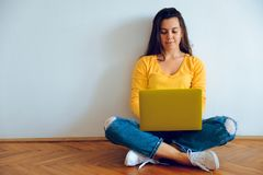 Young pretty woman sitting on the floor with laptop Royalty Free Stock Photos