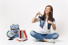 Young pretty smiling woman student pointing index finger on alarm clock sitting near globe, backpack, school books stock photos