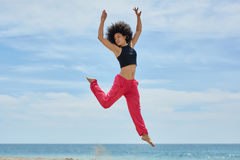 Young pretty sportswoman jumping on beach raising hands. Portrait of young pretty sportswoman jumping on beach raising hands Royalty Free Stock Image
