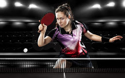Young pretty sporty girl playing table tennis on. Portrait Of Young Girl Playing Tennis On Black Background with lights Stock Images