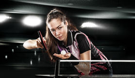 Young pretty sporty girl playing table tennis on. Portrait Of Young Woman Playing Tennis On Black Background with lights stock images