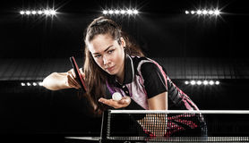 Young pretty sporty girl playing table tennis on. Portrait Of Young Woman Playing Tennis On Black Background with lights Royalty Free Stock Photo
