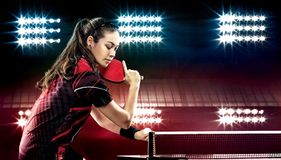 Young pretty sporty girl playing table tennis on. Portrait Of Young Woman Playing Tennis On Black Background with lights Royalty Free Stock Photos