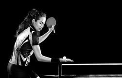 Young pretty sporty girl playing table tennis. Portrait Of Young Woman Playing Tennis On Black Background with lights. Black and white stock photo