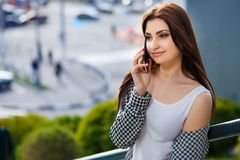 Young pretty stylish happy woman talking on smart phone in the c royalty free stock photo