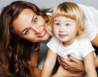 Young pretty stylish mother with little cute blond daughter hugg. Ing, happy smiling real family, lifestyle people concept close up Stock Photo