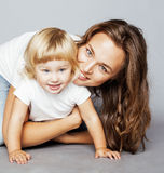 Young pretty stylish mother with little cute blond daughter hugging, happy smiling family, lifestyle people concept. Young pretty stylish mother with little cute Stock Photos