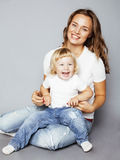 Young pretty stylish mother with little cute blond daughter hugging, happy smiling family, lifestyle people concept. Young pretty stylish mother with little cute Stock Photography