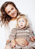 Young pretty stylish mother with little cute blond daughter hugging, happy smiling family, lifestyle people concept. Young pretty stylish mother with little cute Stock Image