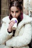 Young pretty stylish teenage girl outside on city street fancy fashion dressed drinking milk shake Royalty Free Stock Photo