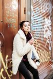 Young pretty stylish teenage girl outside in city wall with graf. Young pretty stylish teenage girl outside at city wall with graffity smoking cigarette at Royalty Free Stock Photo