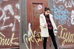 Young pretty stylish teenage girl outside in city wall with graf Royalty Free Stock Images