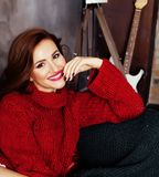 Young pretty stylish woman in red winter sweater at couch in hom Stock Photo