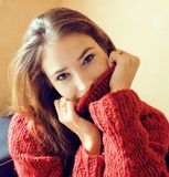 Young pretty stylish woman in red winter sweater at couch in hom Stock Photography