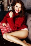 Young pretty stylish woman in red winter sweater at couch in home interior happy smiling, lifestyle people concept Royalty Free Stock Photos