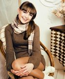 Young pretty stylish woman in winter sweater at couch in home in Royalty Free Stock Photography