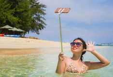 Young pretty and sweet Chinese Asian woman on the beach taking selfie picture portrait with mobile phone camera enjoying holiday h Stock Photo