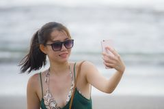 Young pretty and sweet Chinese Asian woman on the beach taking selfie picture portrait with mobile phone camera enjoying holiday h Royalty Free Stock Photography