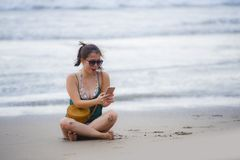 Young pretty and sweet Chinese Asian woman sitting on the beach using  mobile phone sending text and chatting happy Stock Photo