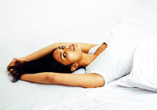 Young pretty tann woman in bed among white sheets having fun, tr Stock Photos